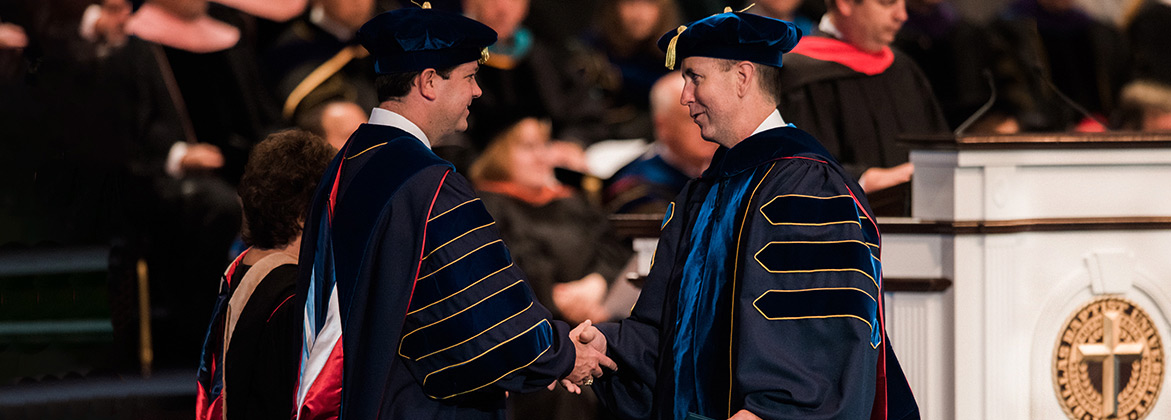 Dr. Wright is shaking hands with a graduating doctoral student.