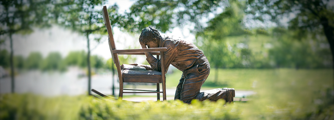A statue of a man kneeling in prayer