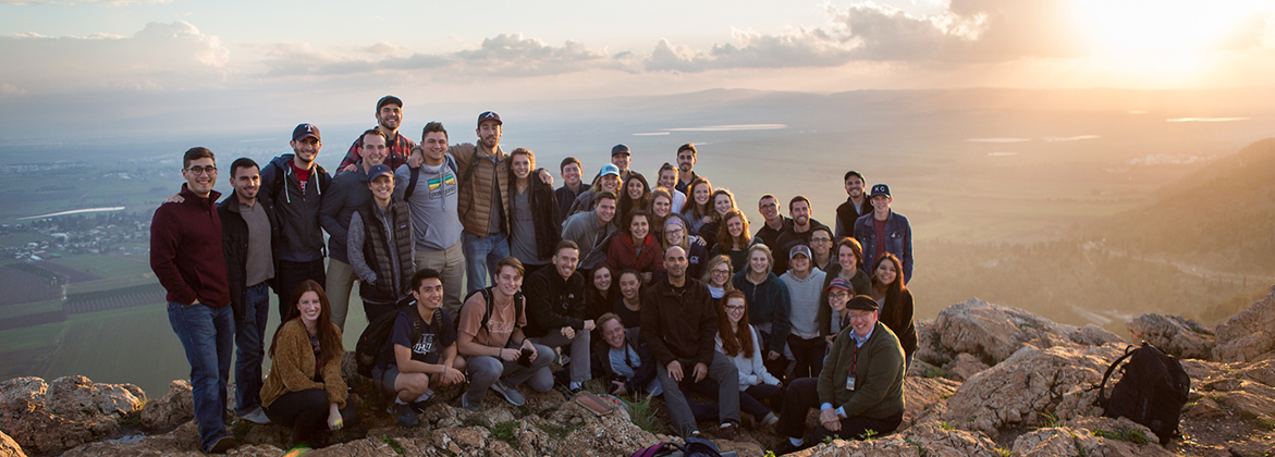 A group of DBU students smile with an Israeli valley in the background