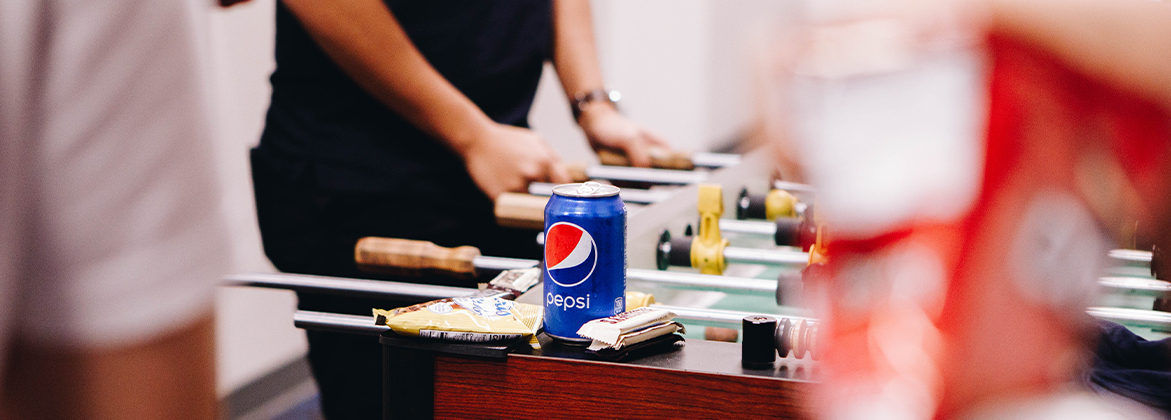 Pepsi can with students playing pool in the background