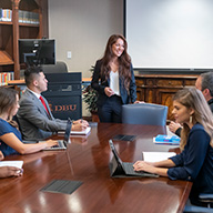Students in a simulated business meeting